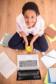 image of mulatto  - Young smiling mulatto schoolgirl sitting on the floor with some books and holding an apple in hands - JPG