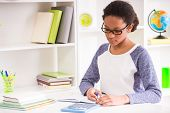 stock photo of mulatto  - Young mulatto schoolgirl in glasses sitting at the table and writing homework on colorful background - JPG