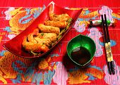 image of deep  - traditional Vietnam deep fried shrimp and pork rolls in breadcrumbs served on a traditional bamboo place mat - JPG