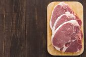 foto of pork chop  - Raw pork chop steak on wooden background - JPG