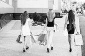 image of girl walking away  - Girls holding shopping bags and walk around the shops - JPG