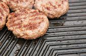 picture of beef-burger  - Beef burgers cooking on a metal griddle - JPG