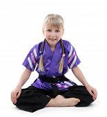 stock photo of karate-do  - Little girl in kimono doing exercises isolated on white - JPG