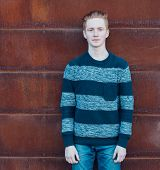 stock photo of redhead  - Young redhead man in a sweater and jeans standing next to a wall - JPG