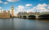 foto of westminster bridge  - Big Ben and the Houses of Parliament in London with Westminster Bridge and the River Thames in the foreground against a blue sky with fluffy white clouds - JPG