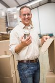 stock photo of tin man  - Smiling warehouse worker holding metal tin can in a large warehouse - JPG