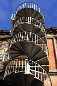 image of spiral staircase  - External metal spiral staircase fire escape in sunlight - JPG
