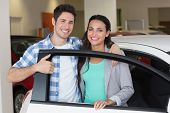 stock photo of showrooms  - Smiling couple in a car shop at new car showroom - JPG