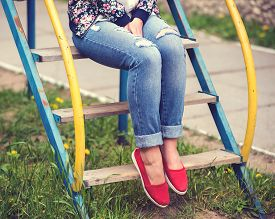 stock photo of chute  - Girl sits on playground chute. Summer concept ** Note: Shallow depth of field - JPG