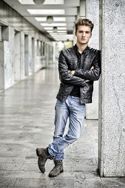 image of jacket  - Attractive blond young man with leather jacket standing outside against pillar - JPG