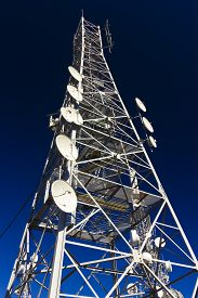 stock photo of antenna  - Communication antenna tower with various antennas on blue sky - JPG