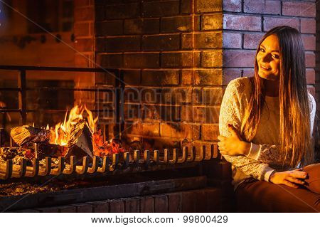 Happy Woman Relaxing At Fireplace. Winter Home.