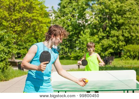 Two boys playing together ping pong outside