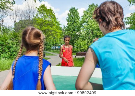 Four teenage friends playing ping pong outside