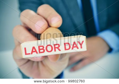 a young caucasian man at his office desk with a rubber stamp with the text labor day