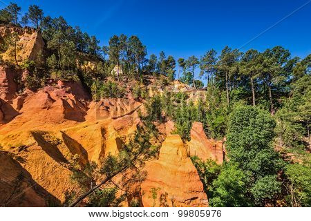 Multi-colored ocher outcrops - from yellow to orange-red. Green trees create contrast with the ocher. Roussillon, Provence Red Village