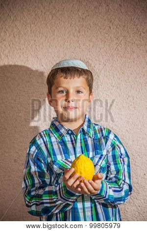 The etrog - ritual fruit for Jewish holiday of Sukkot. The charming seven-year-old boy in white festive skullcap holds citrus in hand