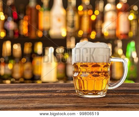 Glass of light beer served on wooden desk. Bar on background