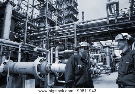 oil and gas engineers inside large petrochemical refinery, blue metal toning concept