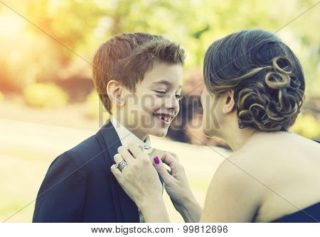 Mother fixing bow tie on son candid moment