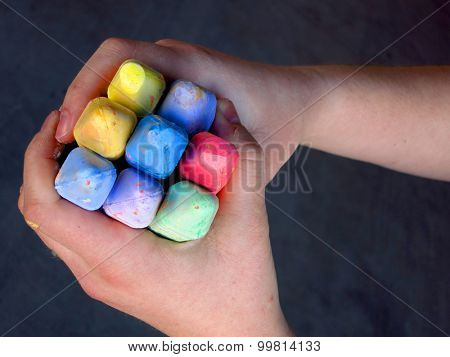Child's hands holding large colored chalk for drawing and art