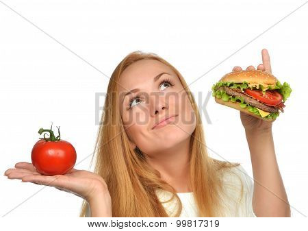 Fast Food Eating Concept Comparing Burger Sandwich In Hand And Tomato