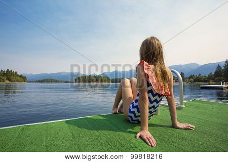 Girl enjoying a Summer Vacation at a beautiful mountain lake. View from behind with a gorgeous rocky mountain scene behind her