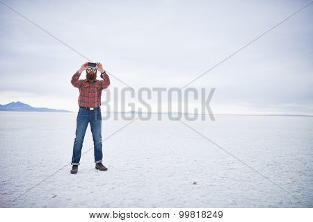 lone bearded hipster in vast desolate salt flats using smartphone to take selfies with copyspace composition
