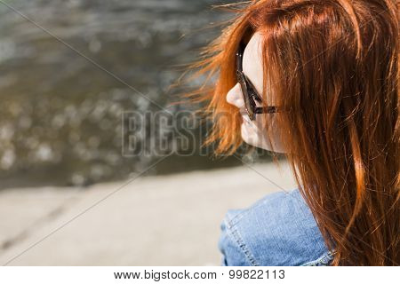 red hair young girl  sitting on a dock