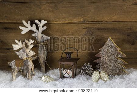 Rustic country style decoration with reindeer, lantern and snow on old wooden background.