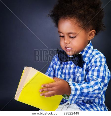 Cute little schoolkid with opening book over blackboard background, preparing to go to first grade, education in elementary school