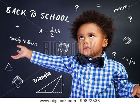 Portrait of smart curly African American schoolboy in the school on math lesson, solving task near chalkboard