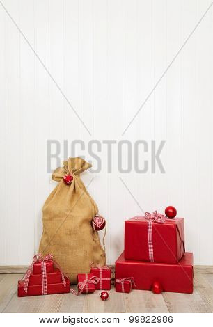 Red christmas presents with santa sack on white wooden wall for decoration.