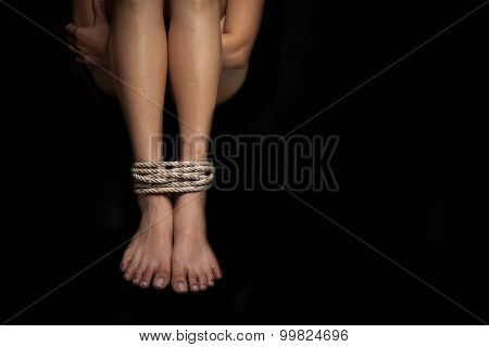 Feet of a missing kidnapped abused hostage victim woman tied up with rope in emotional stress and pain afraid restricted trapped call for help struggle terrified locked in a cage cell.