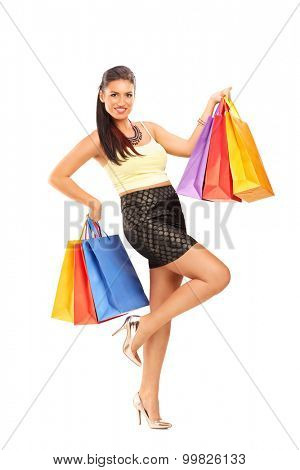 Full length portrait of a beautiful young woman holding few shopping bags and looking at the camera isolated on white background