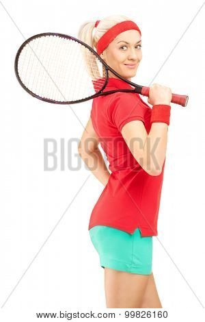 Vertical shot of a young female tennis player holding a racquet and posing isolated on white background