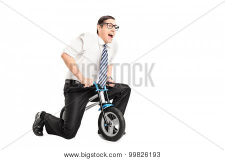 Silly young businessman riding a small bike and looking forward isolated on white background