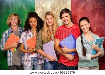 College students holding books in library against italy flag in grunge effect