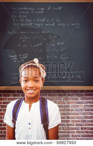 Little girl smiling in school corridor against teal, blue