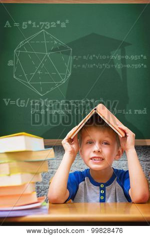 Cute boy with book on head against green