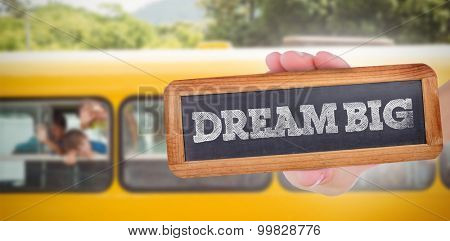 The word dream big and hand showing chalkboard against cute pupils smiling at camera in the school bus
