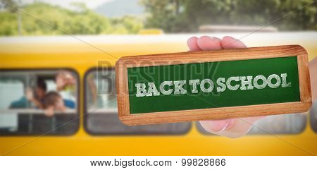 The word back to school and hand showing chalkboard against cute pupils smiling at camera in the school bus