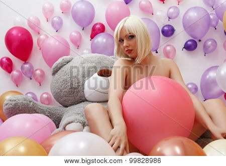 Sexy blonde posing nude in studio with balloons