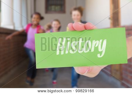 The word history and hand showing card against cute pupils running down the hall
