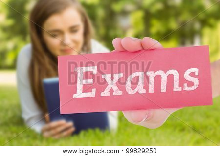 The word exams and hand showing card against university student lying and using tablet pc