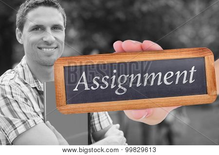 The word assignment and hand showing chalkboard against happy student smiling at camera outside on campus
