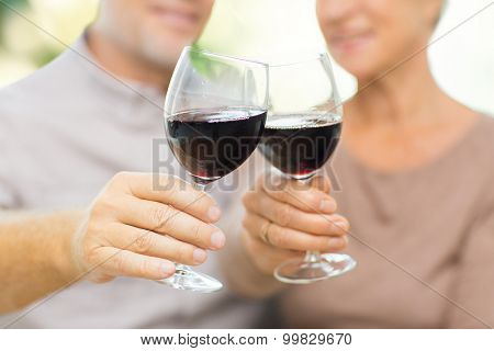 family, holidays, drinks, age and people concept - close up of happy senior couple clinking glasses with red wine over natural background
