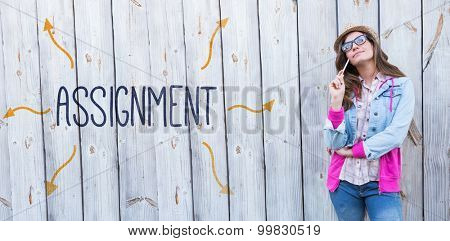 The word assignment against thoughtful woman holding paint brush