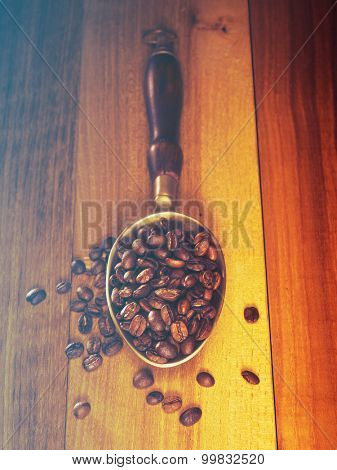 Coffee beans on wooden board with metal scoop.Filtered image: cool cross processed vintage effect.