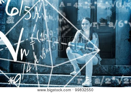 Math problems against smiling student sitting and holding book